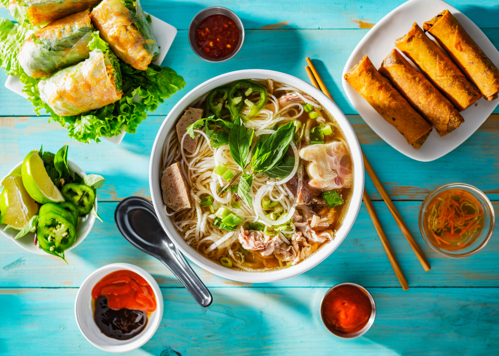 Summery image of a bowl of phở on an aquamarine picnic table, surrounded by condiments and side dishes.