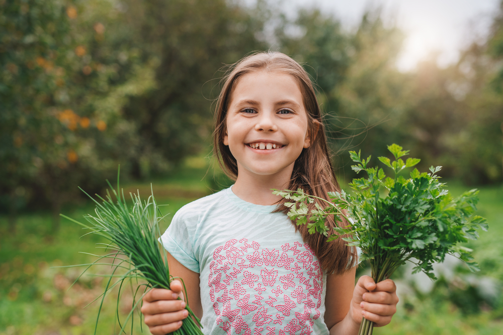 A smiling girl holds freshly grown herbs.