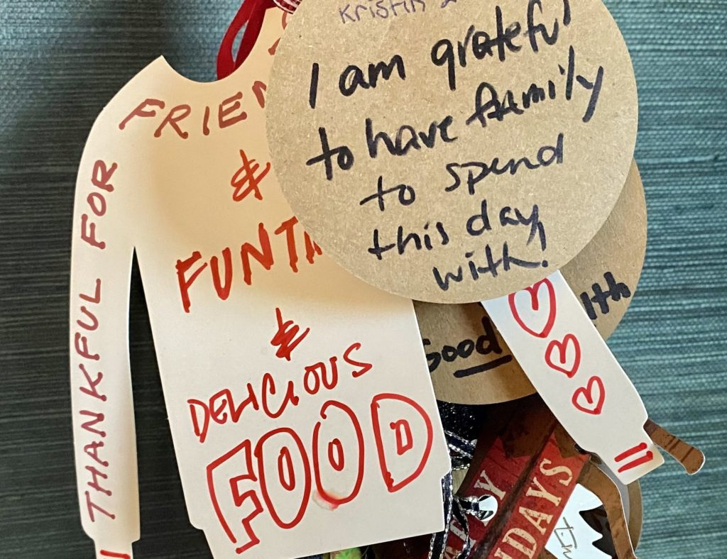A photo of handwritten, paper holiday tags expressing sentiments of gratitude.