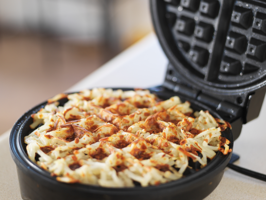 Shredded hashbrowns cooking in a waffle iron